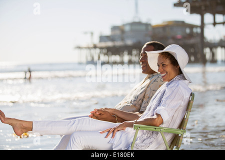 Couple relaxing in lawn chairs on beach - Stock Photo