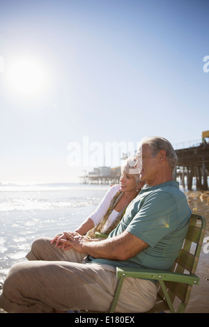 Senior couple relaxing in lawn chairs on beach - Stock Photo
