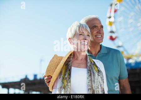 Happy senior couple at amusement park - Stock Photo