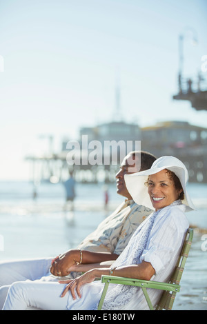 Portrait of couple relaxing in lawn chairs on sunny beach - Stock Photo