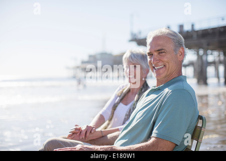 Portrait of senior couple relaxing on sunny beach - Stock Photo