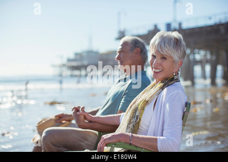 Portrait of senior couple relaxing in lawn chairs on beach - Stock Photo