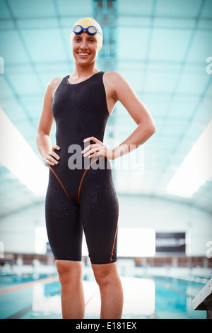 Portrait of confident swimmer standing at poolside - Stock Photo