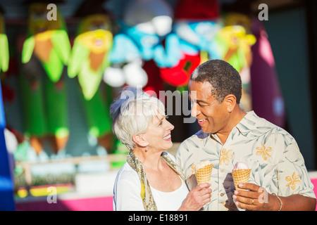 Senior couple eating ice cream cones at amusement park - Stock Photo