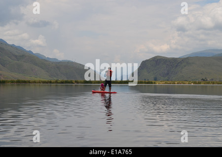 A man Stand Up Paddle Boarding (SUP) with his children on Laguna Huacarapay, in near Cusco, Peru - Stock Photo