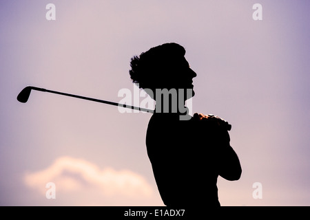 Silhoutte of Golf player watching ball in the distance - Stock Photo