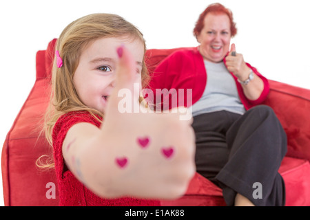 Cute little girl with red hearts painted on her hand giving a thumbs up gesture of approval with her grandmother - Stockfoto
