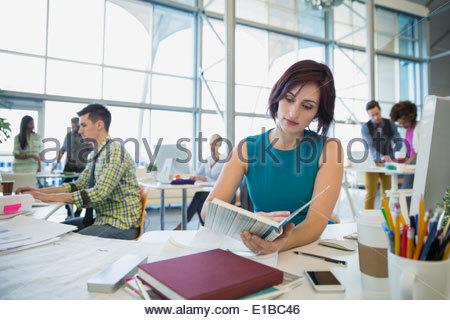 Businesswoman working at desk - Stock Photo