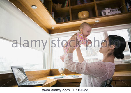 Mother holding baby in home office - Stock Photo