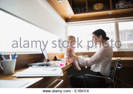 Mother and baby at laptop in home office - Stock Photo