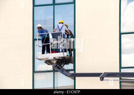 Window cleaners working on a glass facade in a gondola - Stock Photo