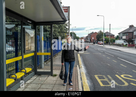 Lady waiting at the bus stop for a bus to come along - Stockfoto
