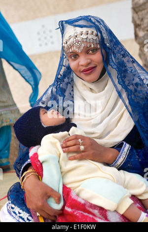 An Omani mother in traditional dress with her baby in Muscat, in the Sultanate of Oman. - Stock Photo