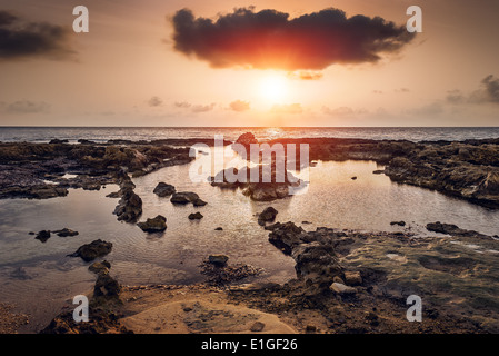 sunset over the sea and rocky coast in Mahdia, Tunisia - Stock Photo