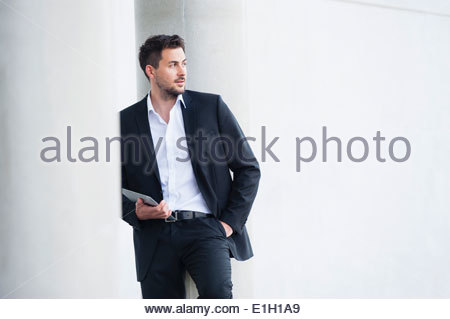 Young businessman leaning against wall with digital tablet - Stock Photo