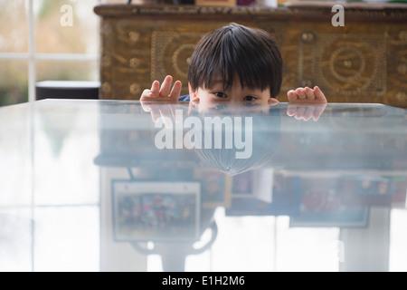 Portrait of boy peeking over dining room table - Stock Photo