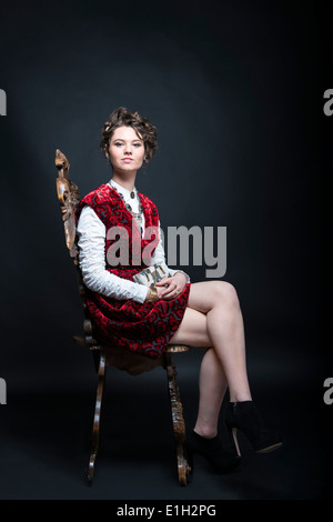 Portrait of beautiful Caucasian model in red Victorian-style velvet dress, seated on wooden chair - Stock Photo