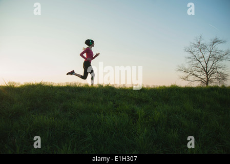 Young female runner silhouetted on hill - Stock Photo