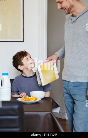 Father pouring cereal into son's bowl - Stock Photo