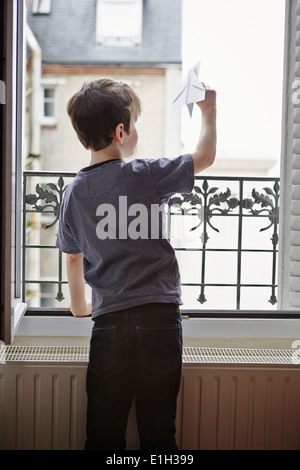 Boy launching paper plane from window - Stockfoto