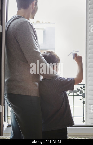 Boy launching paper plane from window - Stock Photo