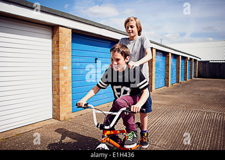 Boys giving friend a ride on bike - Stock Photo
