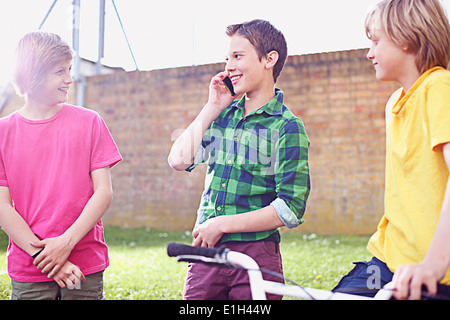 Boy using cell phone with two friends - Stock Photo