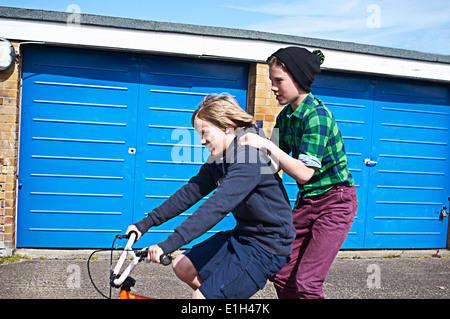 Boy giving friend a ride on bike - Stock Photo