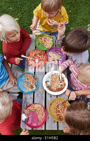 Overhead view of seven children eating spaghetti at picnic table - Stock Photo