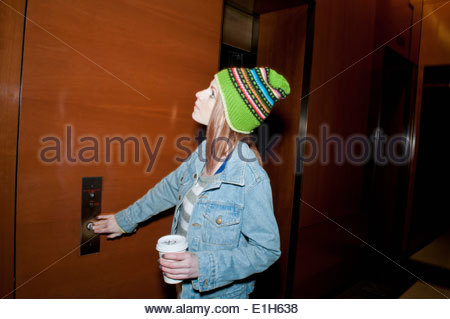 Young woman with takeaway coffee pressing elevator button - Stock Photo