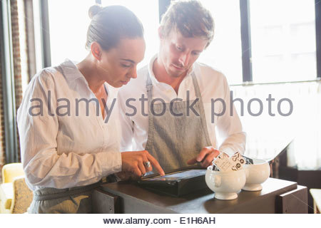 Chef and waitress using digital tablet in restaurant - Stock Photo