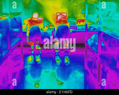 Infra red heat image of workers and heat loss at computer work station - Stock Photo