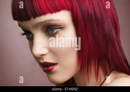 Close up studio portrait of young woman with pink hair - Stock Photo