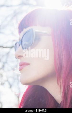 Close up portrait of young woman with pink hair and sunglasses - Stock Photo