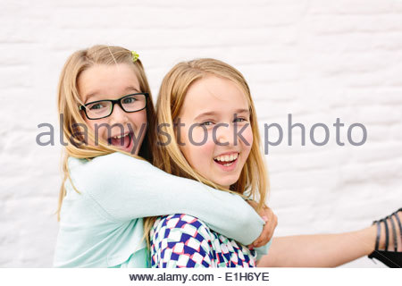 Two sisters playing piggyback - Stock Photo