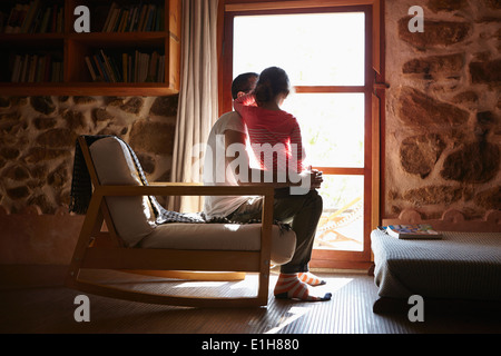 Mid adult man and daughter looking out of window - Stock Photo