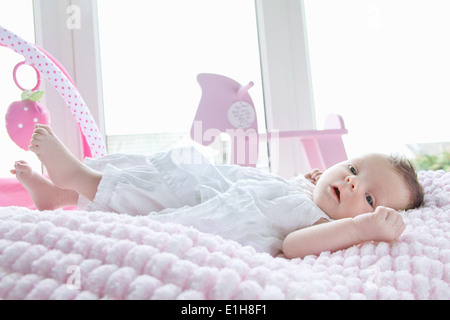 Baby girl lying in bed - Stock Photo
