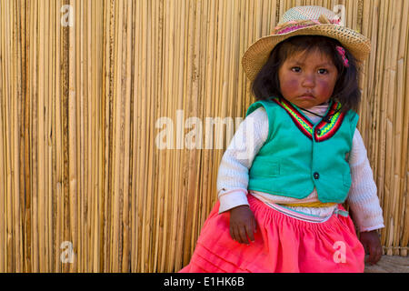 Young girl of the Uro Indians, about 6 years old, wearing traditional dress in front of a reed hut, floating islands - Stock Photo