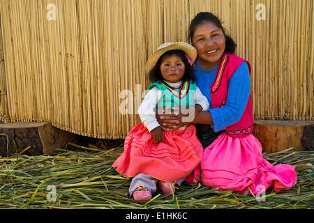 Friendly woman and a girl of the Uro Indians wearing traditional dress sitting in front of a reed hut, floating - Stock Photo