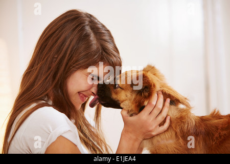 Young woman having face licked by pet dog - Stock Photo