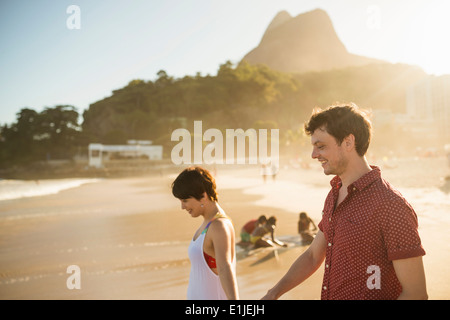 Young couple enjoying sunset, Ipanema Beach, Rio, Brazil - Stock Photo