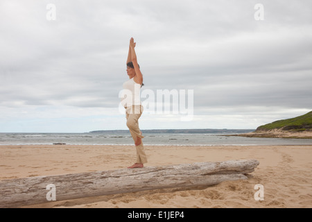 Pregnant mid adult woman practicing yoga on tree trunk at beach - Stockfoto