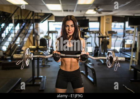 Portrait of mid adult woman weightlifting in gym - Stock Photo