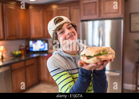 Teenage boy in kitchen holding sandwich - Stock Photo