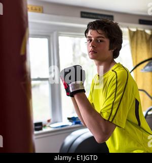 Teenage boy wearing boxing gloves - Stock Photo