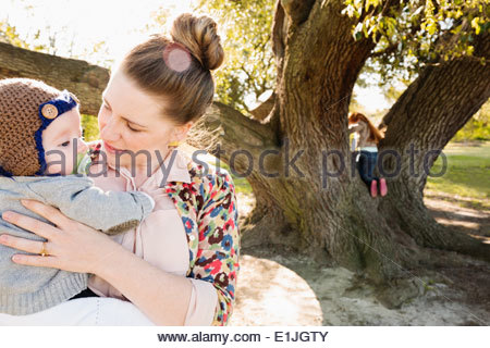 Mid adult mother and baby son in park - Stock Photo