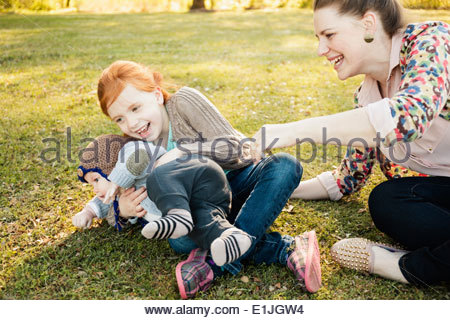 Mid adult mother, daughter and baby son on grass in park - Stock Photo