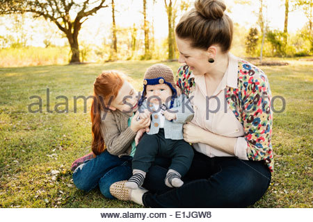Mid adult mother, daughter and baby son in park - Stock Photo