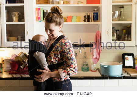 Mid adult mother with baby son in sling in kitchen - Stock Photo
