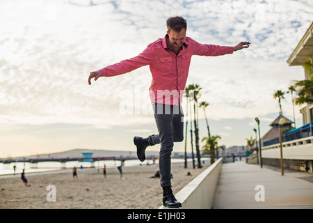 Young man balancing on wall, Long Beach, California, USA - Stock Photo
